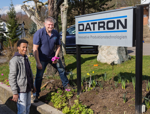 Johannes Stork, employee building management and  new employee Aaron Arefe Mesegna from Eritrea work in the garden at DATRON AG.